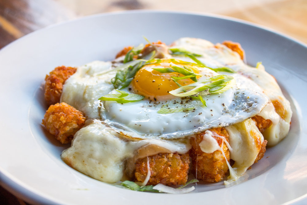 Breakfast Poutine - Maple sausage gravy, tater tots, cheddar cheese curds, and sunny side egg