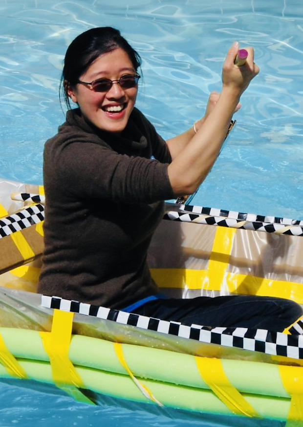 A woman tests a boat built during a team building exercise
