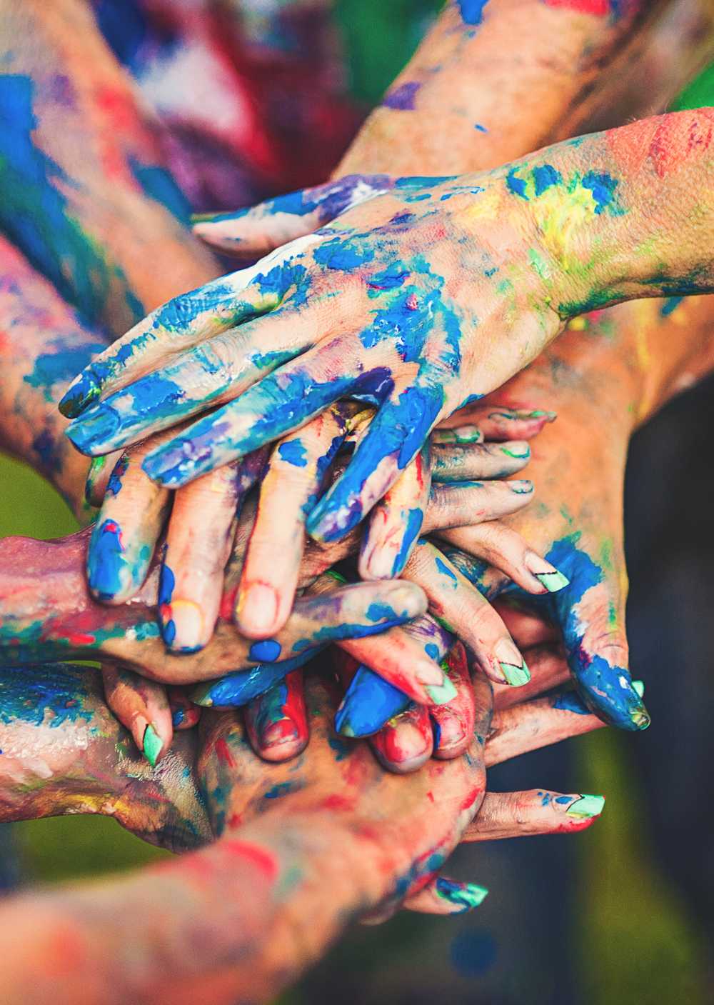 Paint covered hands join together after a team building event