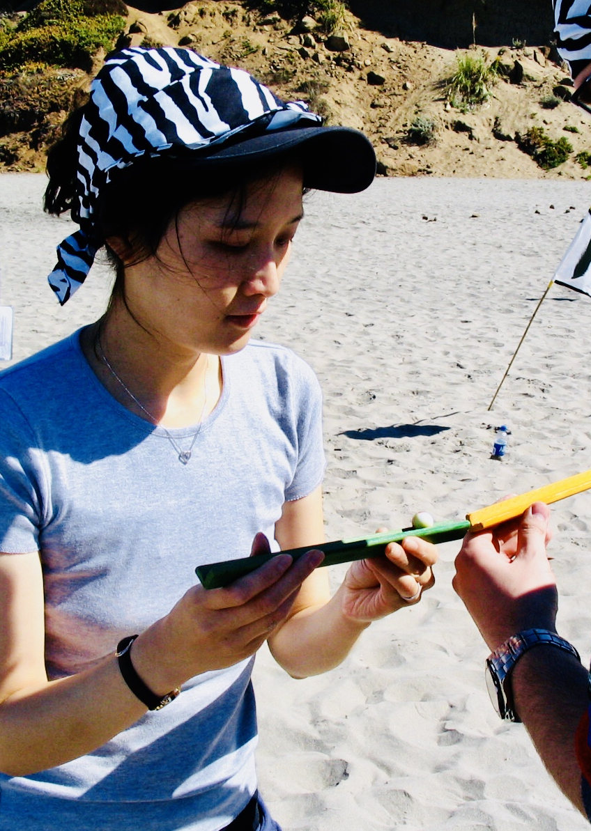 A woman analyzes a clue during a team building event on the beach