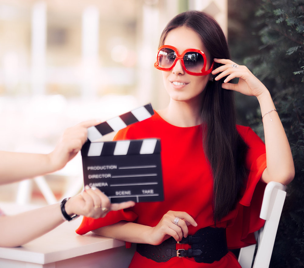 An actress prepares to shoot a scene as a stage hand holds the clapperboard.