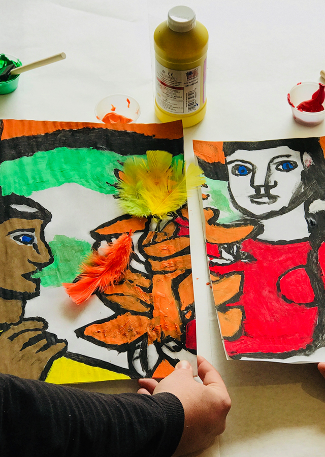 Two participants work to create a mural divided into several sections.