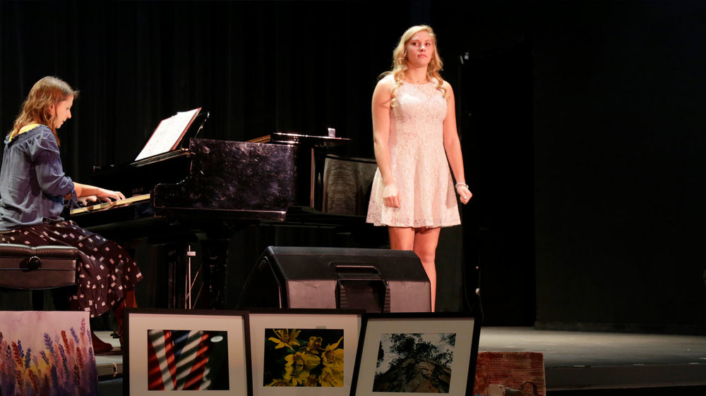 A student is preparing to sing with her mentor playing piano