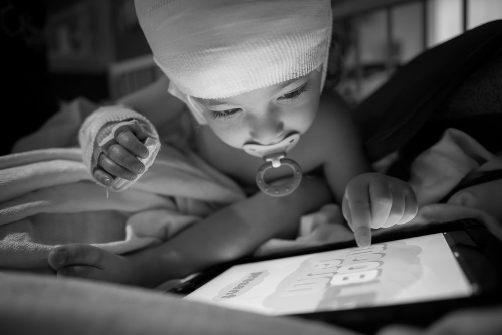 In her hospital bed, Arianna passes time by playing with her iPad. During her observation visits, Arianna stays in her hospital room without leaving for days at a time. Arianna suffers from Tuberous Sclerosis, a rare genetic disease that causes benign tumors to grow in her brain, heart, and kidneys.