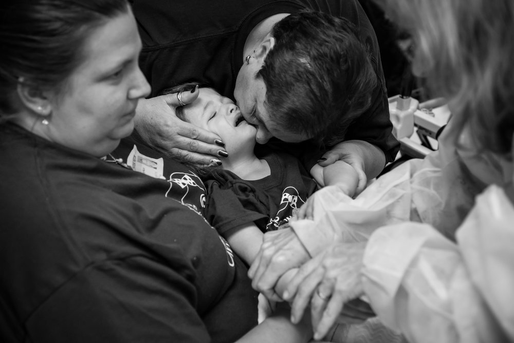 A doctor removes Arianna's IV as she cries in her mother's arms and her grandmother attempts to comfort her. Arianna's parents worry about her doctors not being aggressive enough, and have considered alternative treatment options.
