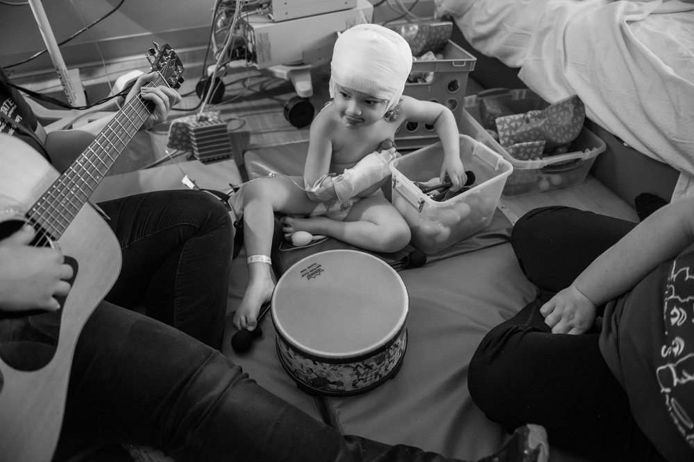 Arianna watches her music therapist play a song while at the hospital for an observational visit.