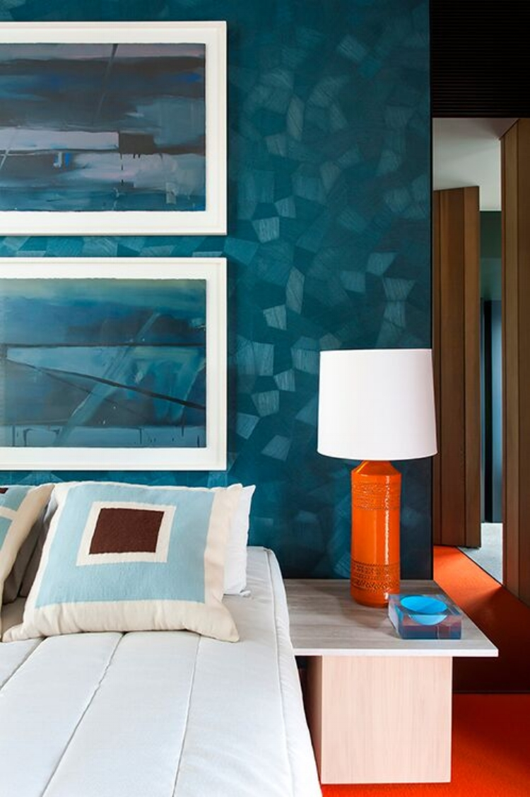 A beautiful blue/teal textured wallpaper is the perfect backdrop to the pops of 'seventies' orange. Interior by  SJB