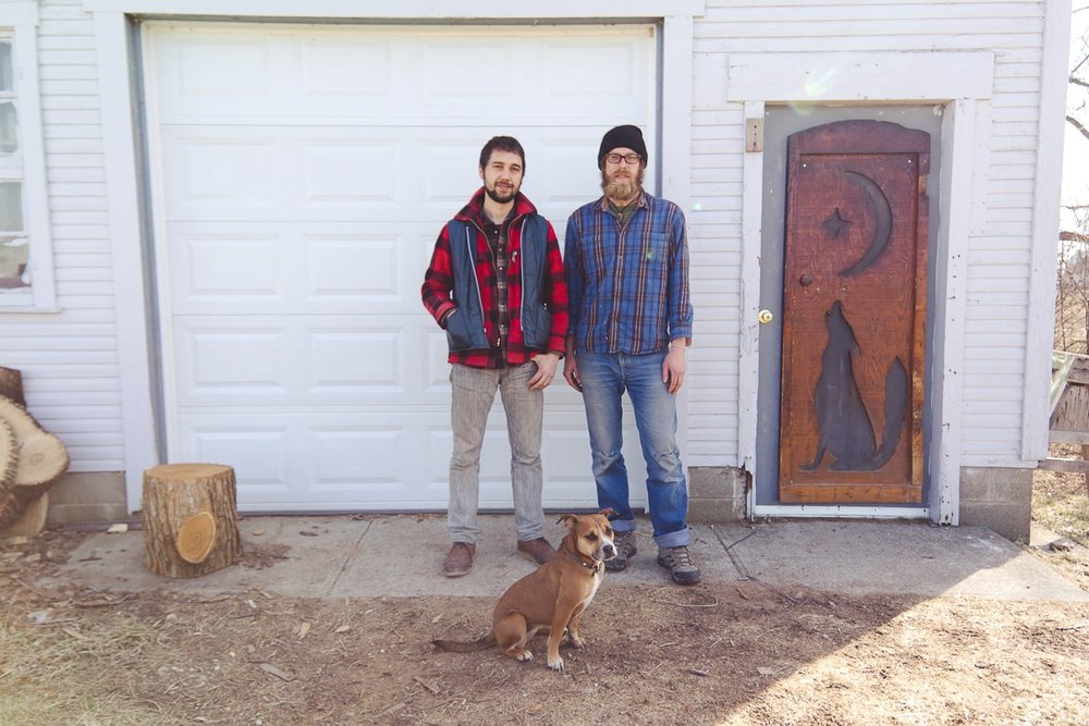 Brett & Dave, with River the dog, in front of their shop