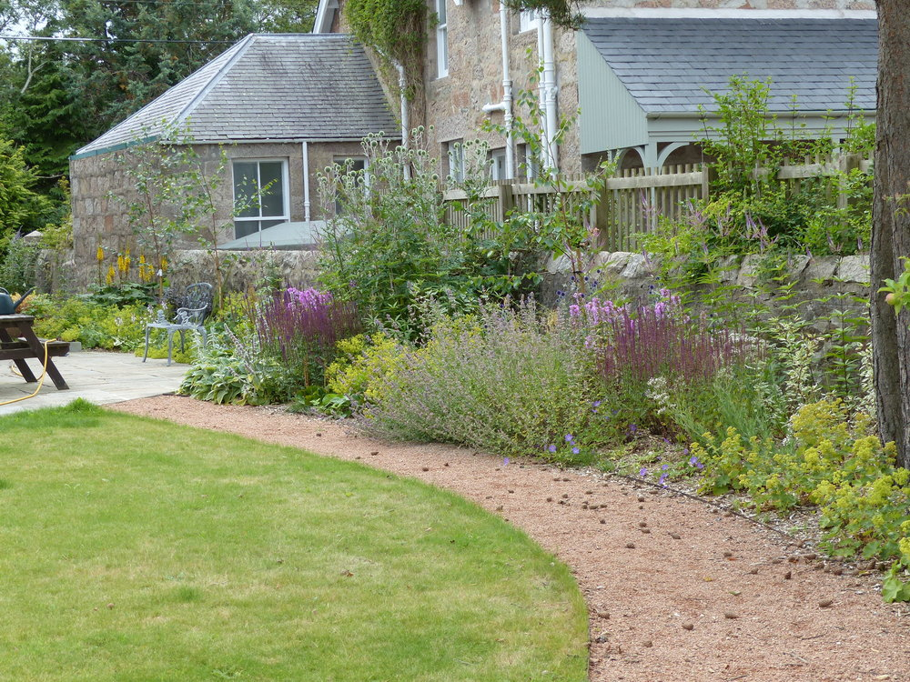 Curved gravel path, lawn and colourful border