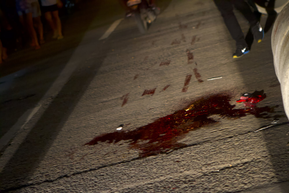 Motocycles and cars dragged the blood of 16-year-old Aldrin Jore through the streets of Quezon City, Manila, after he was gunned down by unknown assailants after going out for a haircut.