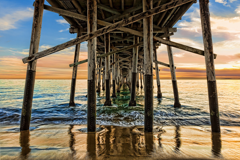 Looking under the Balboa Pier with the splashing water and sunset colors in Newport Beach, CA.