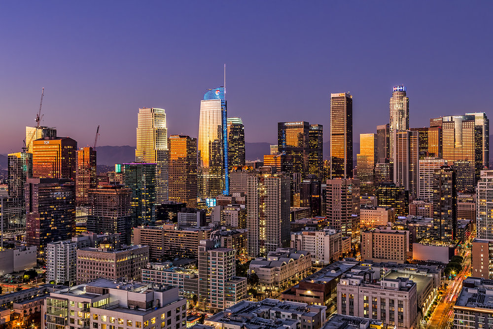 Los Angeles skyline now in 2017 with a golden glowing light at dusk.