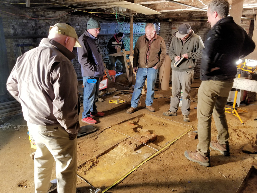 the team examining a discovered foundation in the basement