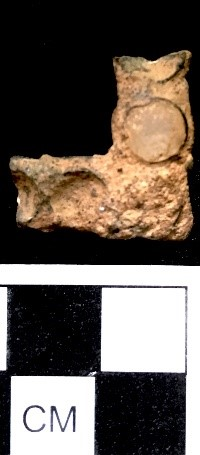 Figure 1. copper alloy shoe buckle with glass insets, cloverfields excavations, dining room area.