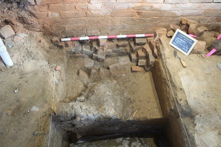 figure 2. feature 341, a wood-lined cellar located in the concrete addition. the ash fill is visible abutting the brick rubble as well as in the profile at the bottom of the photo.