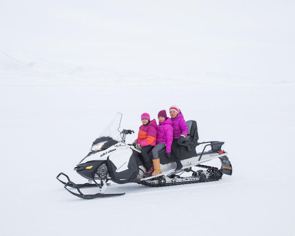 Taryn, 10, drives her friends on her parents' snowmobile on the sea ice near Arctic Bay.