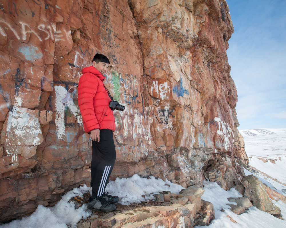 Photo workshop participant Ruben, near the summit of one of the mountains surrounding Arctic Bay.