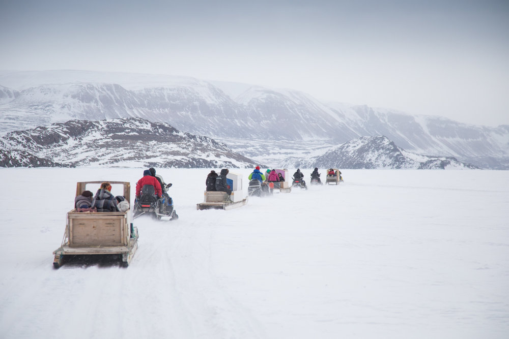 A train of snowmobiles pull high school students on  qamutiks  to Arctic Bay's school camp.