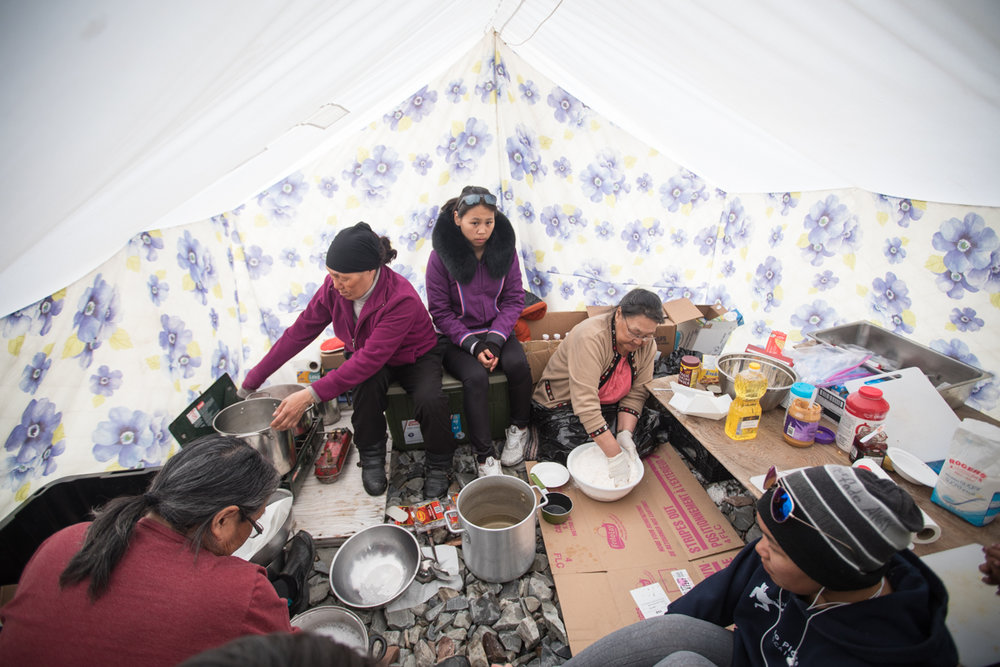 In a floral-patterned tent, elders Tootalik, Hannah and Tagoonak teach bannock-making to a group of teenage girls, imparting their perspectives on resourcefulness, feeding a family, and keeping healthy by avoiding processed and sugary foods.