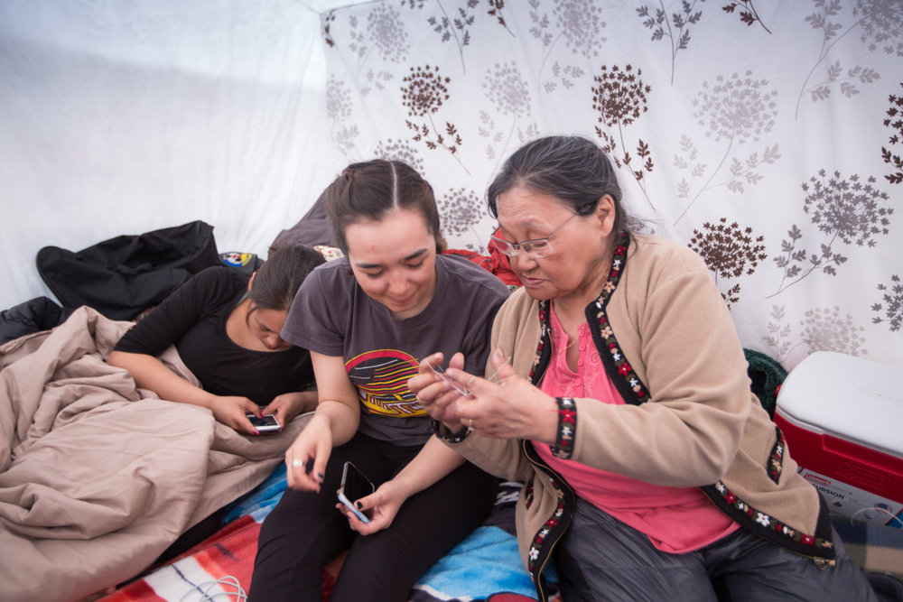 Elder Tagoonak teaches Karen, 17, how to play a traditional game with string.