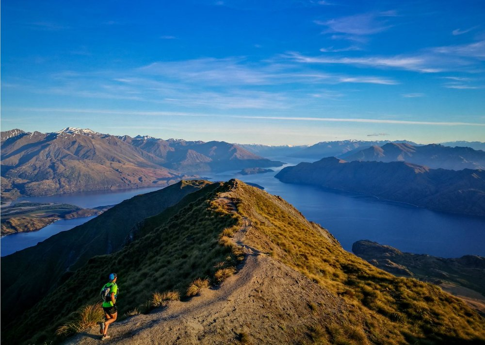 The Classic trail running tour takes in the best of what Queenstown, Wanaka and the surrounding area has to offer.   The Classic  combines one full day mountain run plus two half day runs, and a couple of optional extras. We explore the Oteake Conservation Park, wrestle with Roys Peak and battle with Ben Lomond in Queenstown.  Those eager enough also have the chance at some optional extras, including a recovery run or ride on some of the scenic Central Otago Rail Trail, a sunset run up Queenstown Hill, plenty of exploration to soak it all in and self selected recreation time that could include anything from luge rides to downhill mountain biking.  We will cover approximately 60-70km over the tour and around 3000m+ of elevation, all sandwiched between arrival and departure days either side.   Difficulty  The terrain and distances are sure to challenge, so you do need to take note of distances, terrain types and your fitness levels. However, our style remains holiday-esque, so don't bring your game face except when facing the mountain itself. RunAways are holidays tours. We encourage anyone with the stamina to join our tours. While our tours may be physically very demanding, speed is irrelevant and we are non-competitive. This isn't a training camp, it's a holiday, just like no other! If you have any questions about your fitness, please get in touch.   Itinerary Summary   Day 1 | Arrival: Start with our first meet up at Queenstown Airport. Meet team and tour briefing.  Day 2 | Oteake Conservation Park: A big day to start the tour, with around 30km-35km to shake of any laggy travel legs.  Meals offered: Continental breakfast option   Day 3 | Recovery: Optional recovery run or ride on parts of the Central Otago Rail Trail and time to soak in some of the sights of stunning Wanaka.  Meals offered: continental breakfast option   Day 4 | Roys Peak: Tackle this standout classic after an early start. The goal is a sunrise summit, and a delicious post run meal of course!  Meals: continental breakfast option   Day 5 | Travel & Queenstown Hill Hike: Today we travel, with an option later in the day for a hike up Queenstown Hill to keep those legs moving. Queenstown is our final destination and tonight we prep for our final push tomorrow morning.  Meals: continental breakfast option    Day 6 | Ben Lomond: The iconic Ben Lomond ascent right at the doorstep of Queenstown. Followed up with an afternoon of leisure and celebratory dinner at the Skyline Gondola buffet (at own expense – optional)  Meals: continental breakfast option   Day 7 | Tour End. Group bus available for drop offs at Queenstown Airport or for those staying on in Queenstown, their nearby accommodation.  Meals: continental breakfast option    Inclusions:   Airport pick up & drop off.  Department of Conservation Permits  Guided Runs  Guided recovery and flexibility session  Accommodation  Travel within New Zealand with the RunAways group.  Some breakfast/meal options (Bread, spreads, cereals, milk, coffee and tea) and snacks (some fruit, muesli bars).  Two spirited, experienced & passionate runners as guides.   Exclusions:   Costs of any optional recreation activities, including any hire of equipment, entry fees or contracting third parties for services.  Food and meals outside of the provisions mentioned in Inclusions.  Individual optional travel outside of group activities and local area transfers.  Flights not included    Please note: We have done our utmost to ensure all material published on this web page is accurate and up to date. However, any and all actual tour details can be updated from time to time. Final confirmation of any details must be made direct with the organisors and are reflected in the Administration Pack.