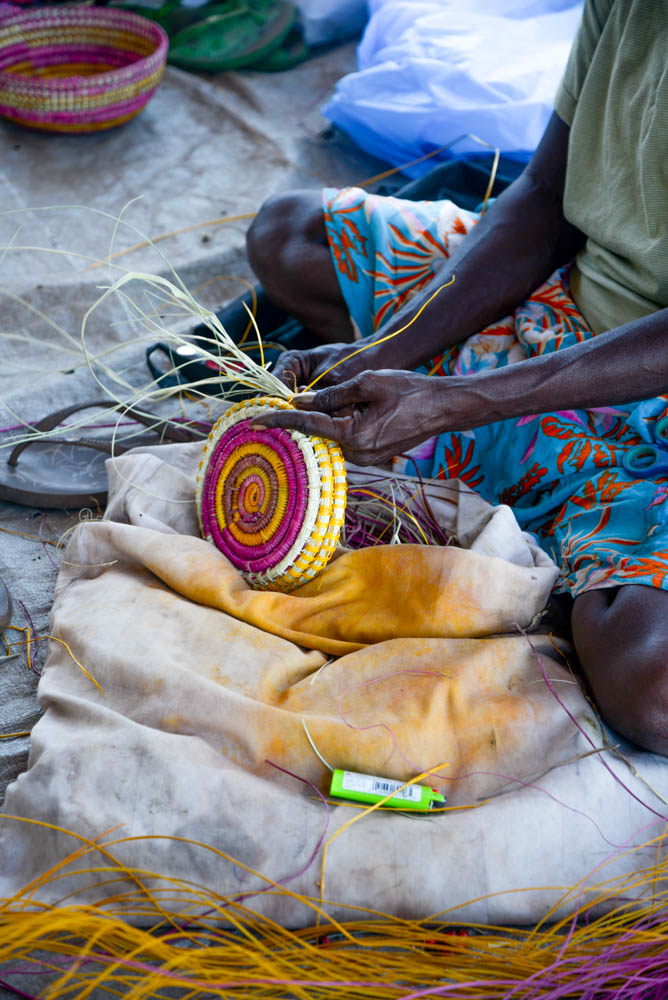 A woman weaving a pandanus basket at Injalak Arts & Craft Centre