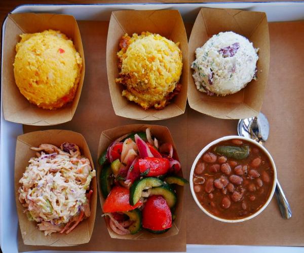 Cheese Grits, Corn Casserole, Potato Salad, Cajun Slaw, Beans, & Cucumber Tomato Salad.