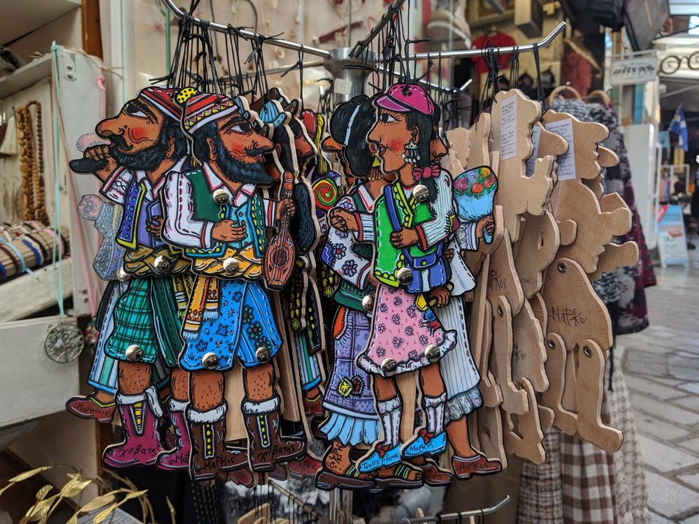 Shop your favorite souvenirs in Athens flea markets. Here you can see Karagiozis figures. Source: Truevoyagers