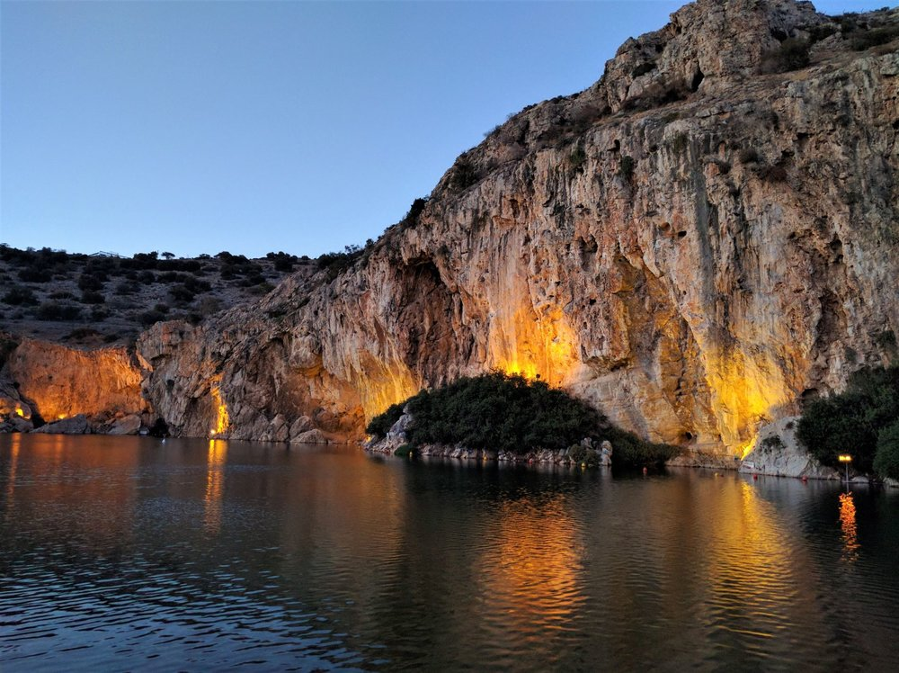 Lake Vouliagmeni at dusk. The lights make the rock formations even more dramatic at night.