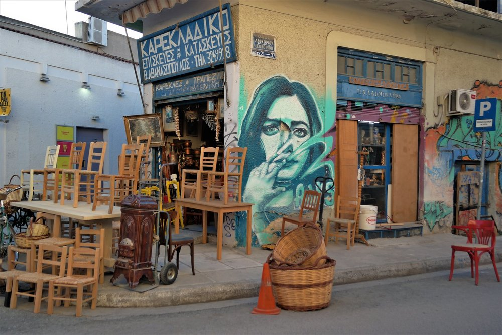 Leokoriou str. mural by Achilles in Psyrri neighborhood of Athens. Street art blends beautifully with local traditional shops.