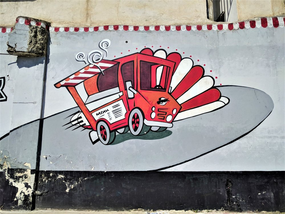 Cute red truck on an old building at Gazi.