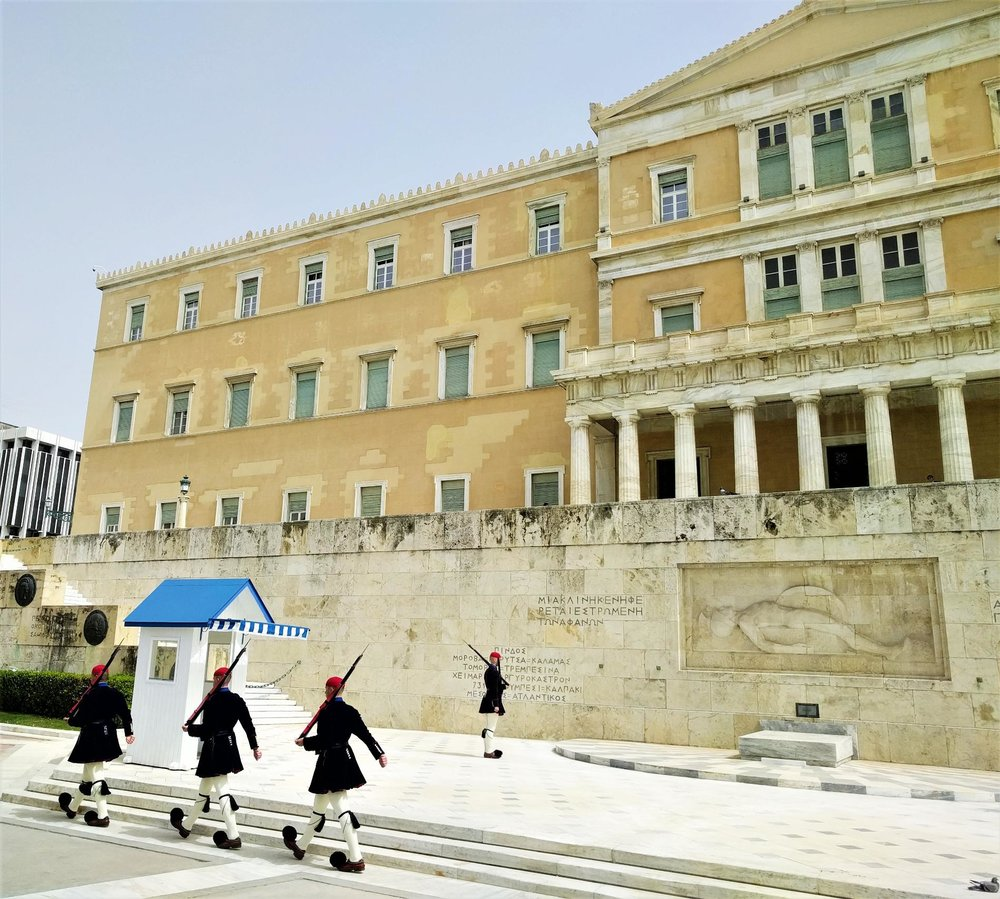 The Parliament guards ( tsoliades  or  evzones ), wearing the traditional uniforms and shoes ( tsarouchia ), march in front of the Greek Parliament building during their hourly change. Source: Truevoyagers