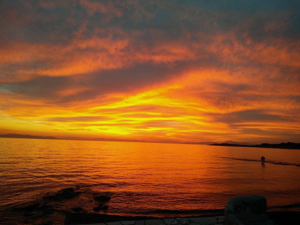 "The sky ""on fire"" during sunset in Voula. Source: Truevoyagers"