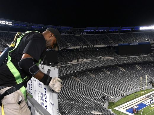 High above the field, a worker replaces a New York Giants placard for the Jets on MetLife Stadium's ring of honor. Photo: Danielle Parhizkaran/Northjersey.com
