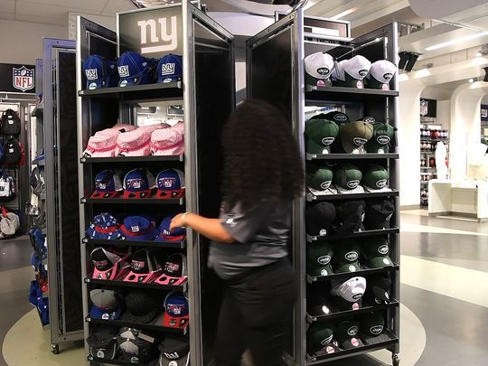 A MetLife Stadium worker flips the hat display in the team store. The display comes out of the wall and spins around to show either the Jets or the Giants merchandise.  Photo: Danielle Parhizkaran/Northjersey.com