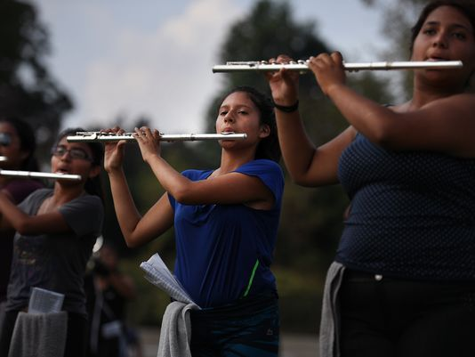 Julie Vazquez, 17, center, practices the flute with the Passaic High School marching band three days after a fire consumed her family's apartment.  Photo: Michael Karas/Northjersey.com