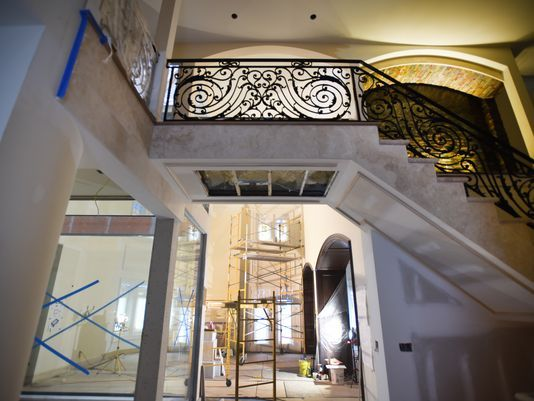 The foyer of a mansion in Saratoga Springs. The glass, to the left, encases an indoor atrium. All design work for the home was completed in downtown Paterson, where drug dealers operate in plain sight.  Photo: Mitsu Yasukawa/NorthJersey.com