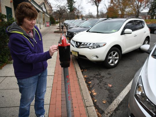 Kathleen Mulvihill of Saddle Brook paying the meter after pulling into parking spot No. 24.  Photo: Michael Karas/Staff photographer