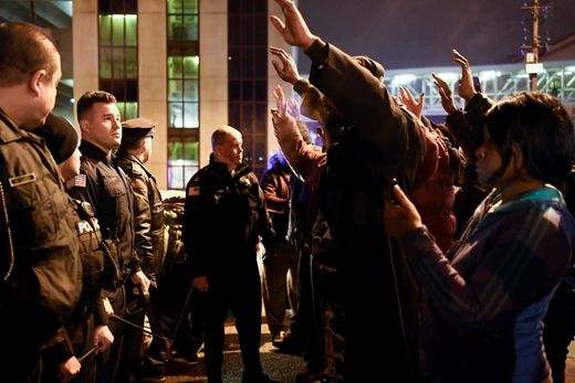 Protesters raise their hands as they face Paterson police officers.  Photo: Danielle Parhizkaran/Northjersey.com