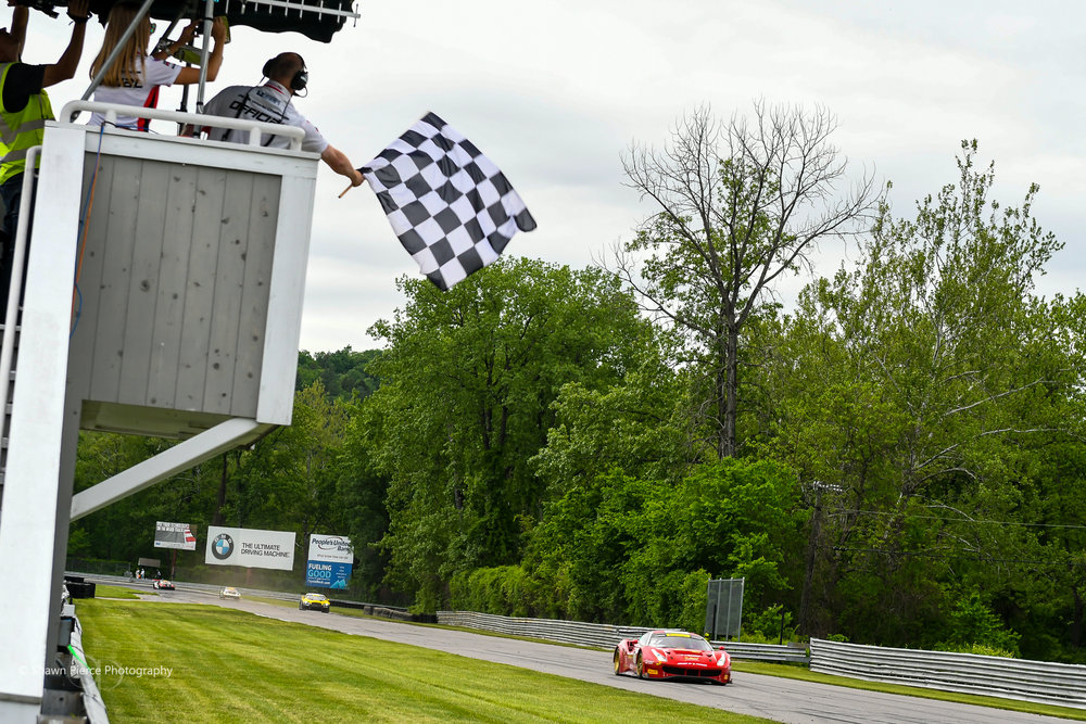 The #61 Ferrari crosses the finish line first to take the final checkered flag of the weekend.