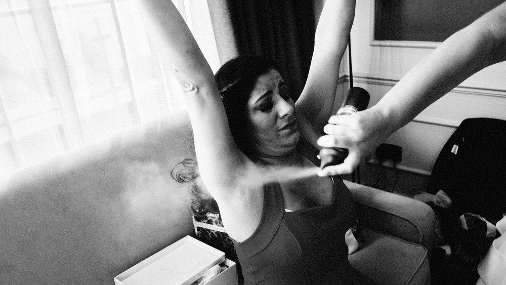 bridesmaid putting on deodorant before wedding in essex