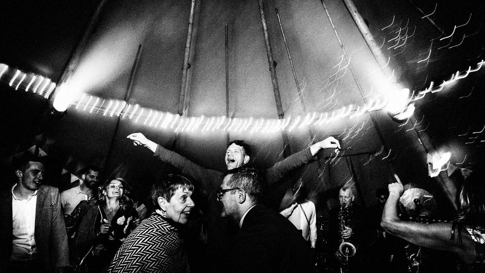 guests partying during a relaxed summer tipi wedding in the peak district