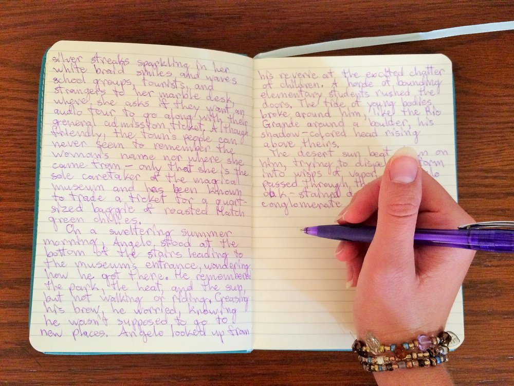 hand holding a pen above a leather notebook with writing on the pages to show how content for websites and blogs is created