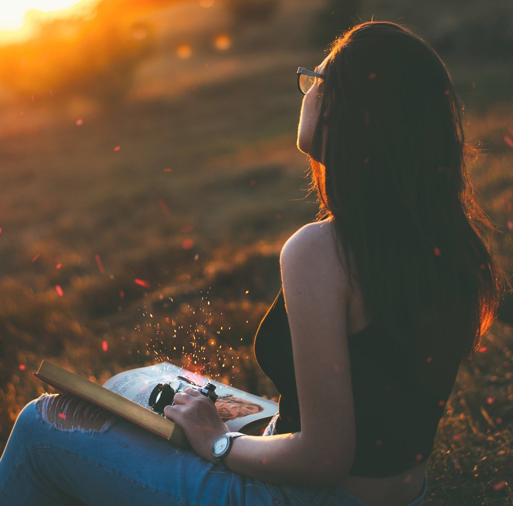 Girl with long hair and glasses sitting n a filed looking at the sunrise with a open book on her lap