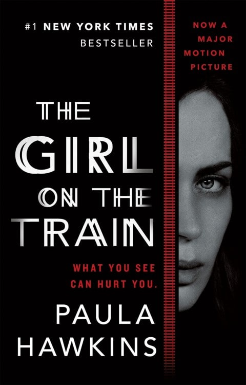 The Girl on the Train book cover with the image of a woman peeking around part of the cover against a black background