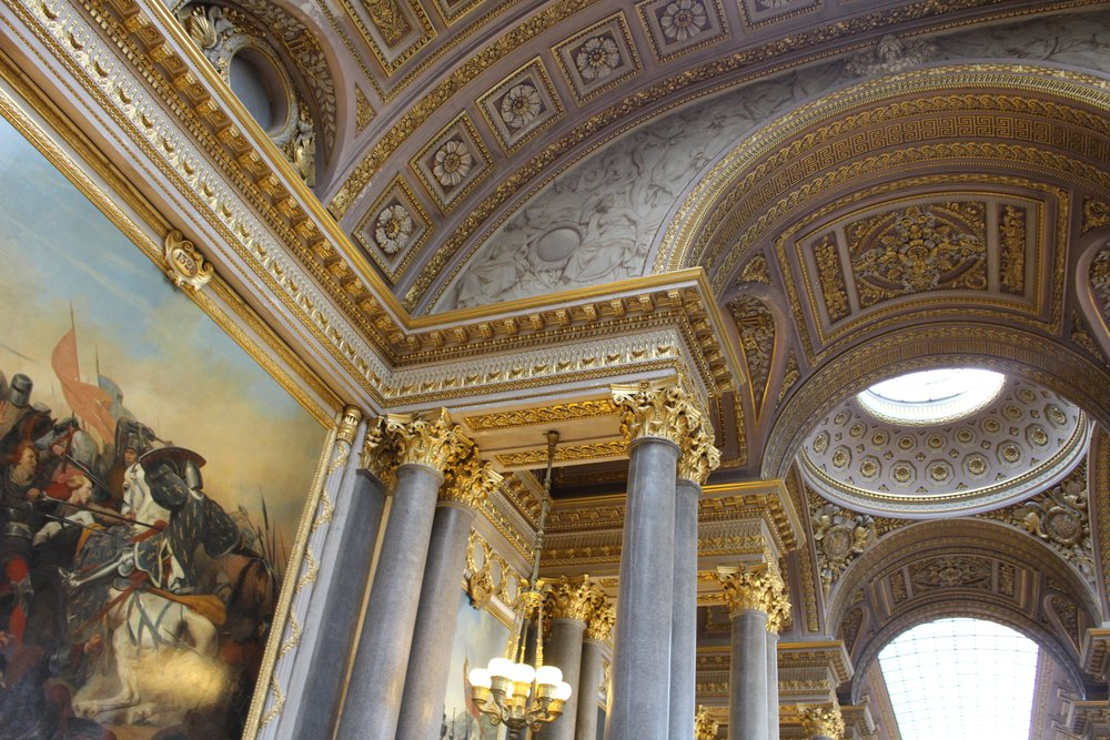 ceiling inside the palace of Versailles with gold molding on granite walls and the top corner of a painting