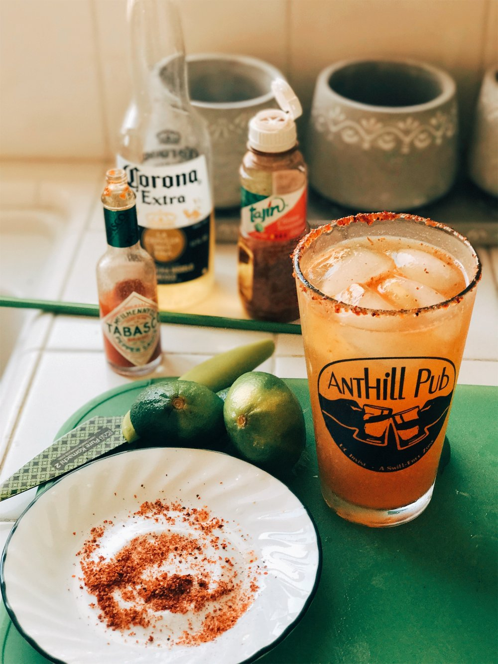 Michelada- A Spicy Farewell - Ingredients: Tajin, kosher salt, 2 limes, 2tsp hot sauce, 1tsp Worcestershire sauce, 1 bottle Corona.Instructions: 1. Pour Tajin/salt in shallow dish in an even layer. Rub a pint with lime, then dip glass into dish. 2. Add lime juice, hot sauce, Worcestershire sauce to pint glass. Add a pinch of salt, fill glass with ice, and top with beer. Stir gently.