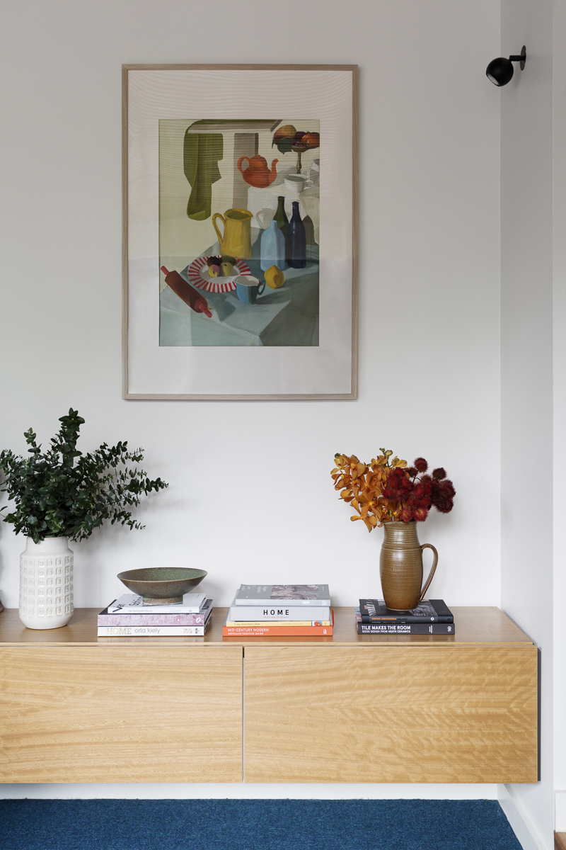 The floating timber veneer  Storage Unit built by Cantilever  provides useful storage in the living room and works in with the palette of finishes for the whole house.  Painting  by Isobel Gordon