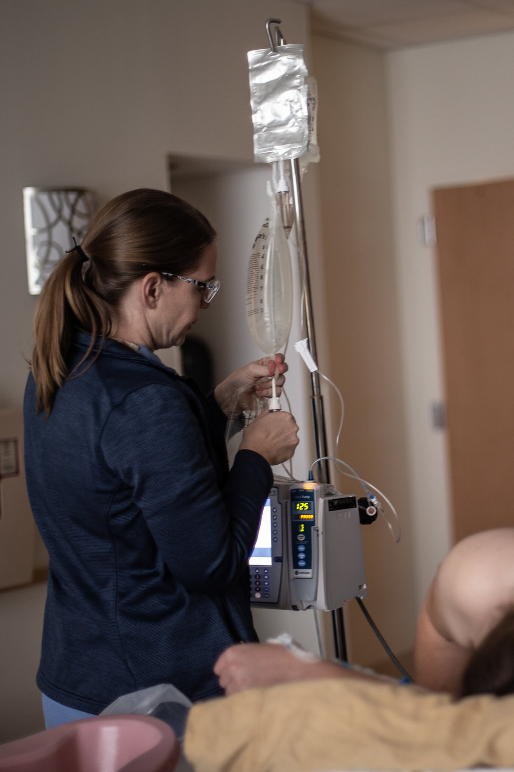 Hospital labor and delivery nurse fills an IV bag.