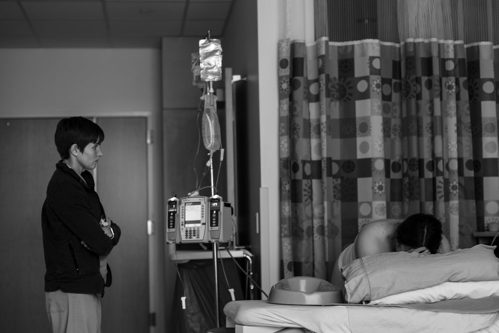 Midwife watches a woman labor in the hospital.